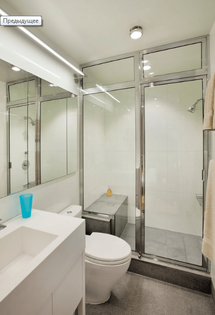 The bathroom is done in minimalist style, with a metallic framed shower and white appliances