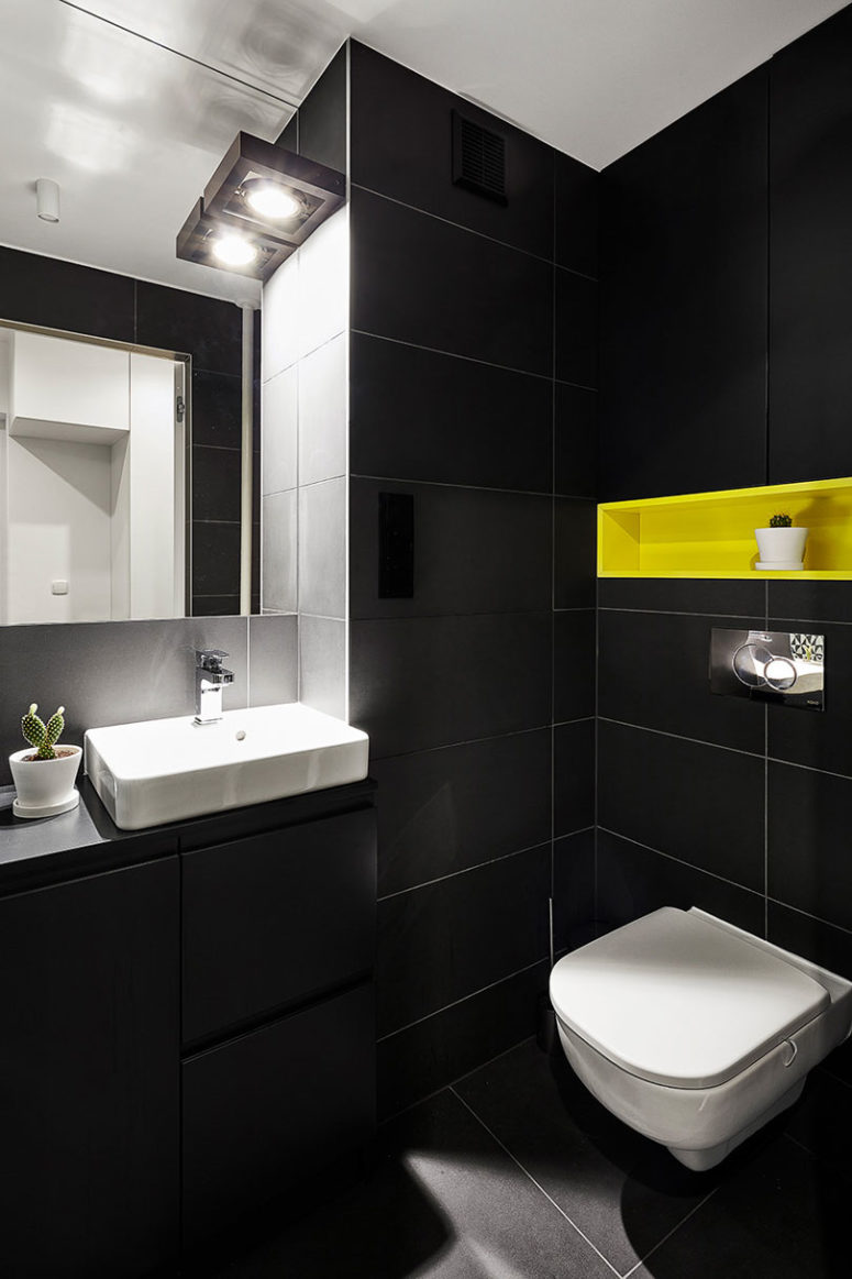 The matte black monochromy is broken with a neon yellow built-in shelf over the toilet
