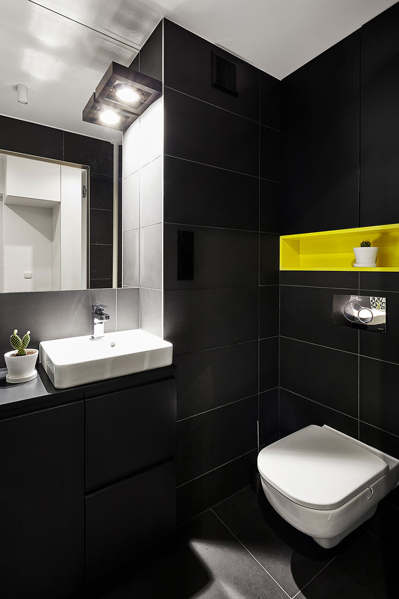The matte black monochromy is broken with a neon yellow built in shelf over the toilet