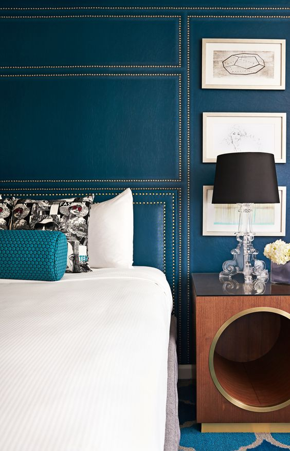 teal wall with decorative nails geo decor looks very chic