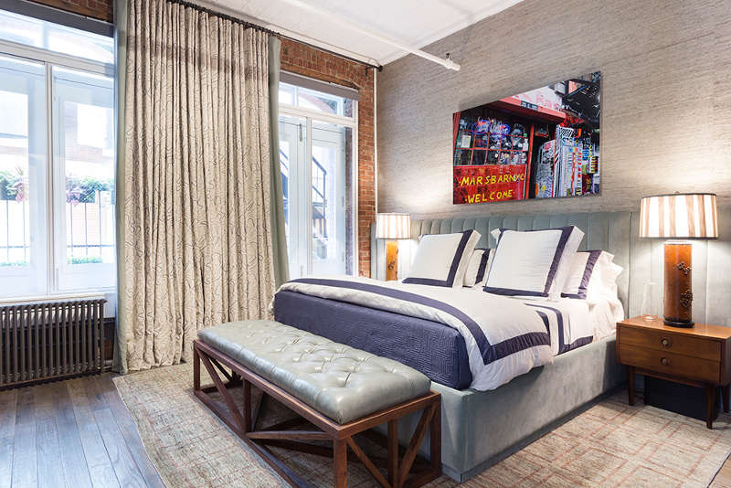 the bedroom is decorated in muted shades and neutrals, there's a grey upholstered bed and bench, an exposed brick wall and a bold photo