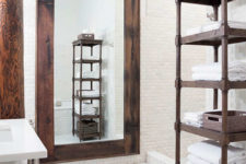 10 The bathroom is clad with white tiles, and the accents are made with dark stained wood and dark metal