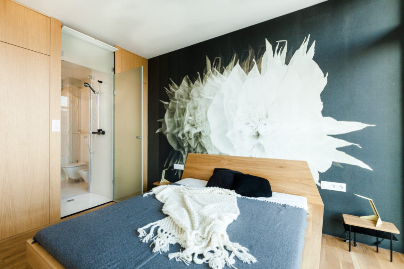 The master bedroom features an oversized floral mural on the headboard wall and a door to the bathroom