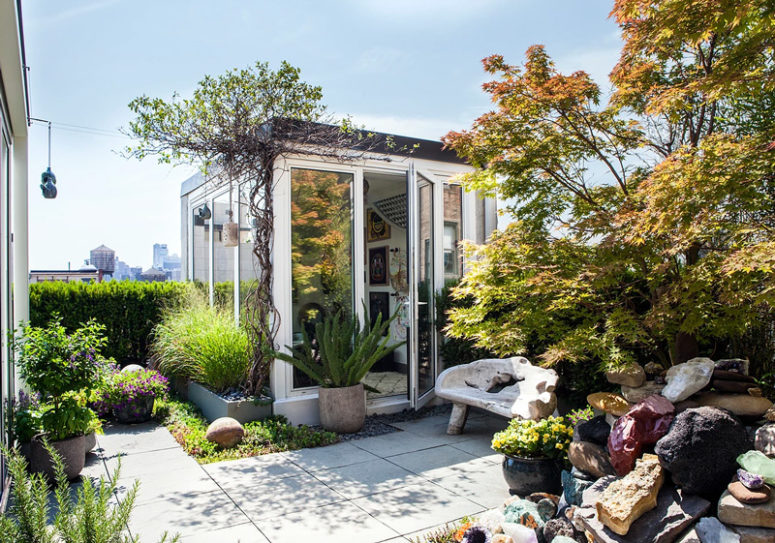 The outdoor space shows much greenery and beautiful rocks as a part of the landscape