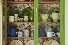 10 a green glass cabinet with colorful floral wallpaper inside for a chic look
