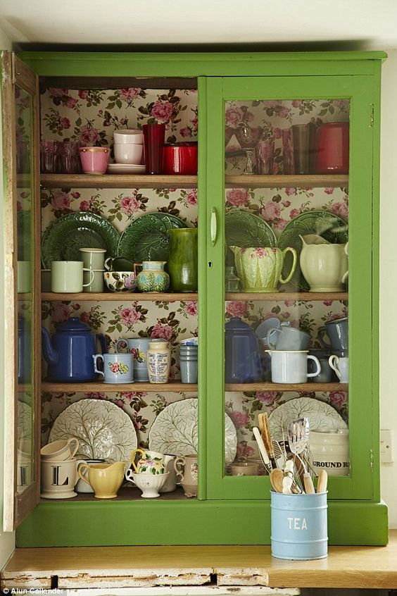 a green glass cabinet with colorful floral wallpaper inside for a chic look