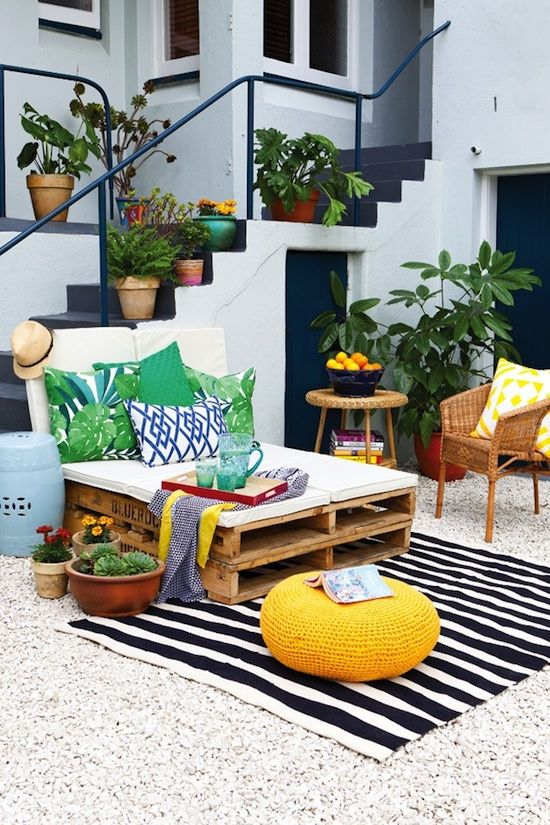 bold print pillows and a striped rug add cheer to this outdoor lounge