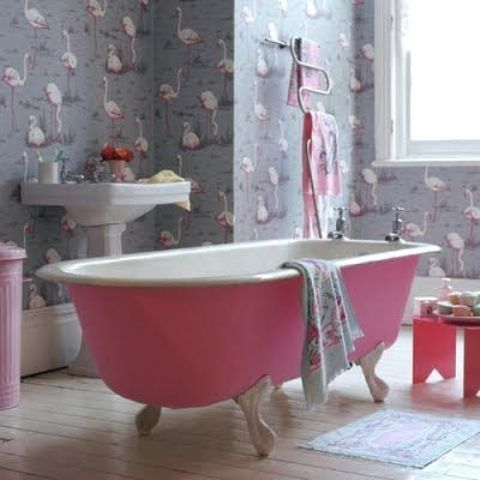 flamingo bathroom wallpaper and a pink bathtub and accessories that highlight it
