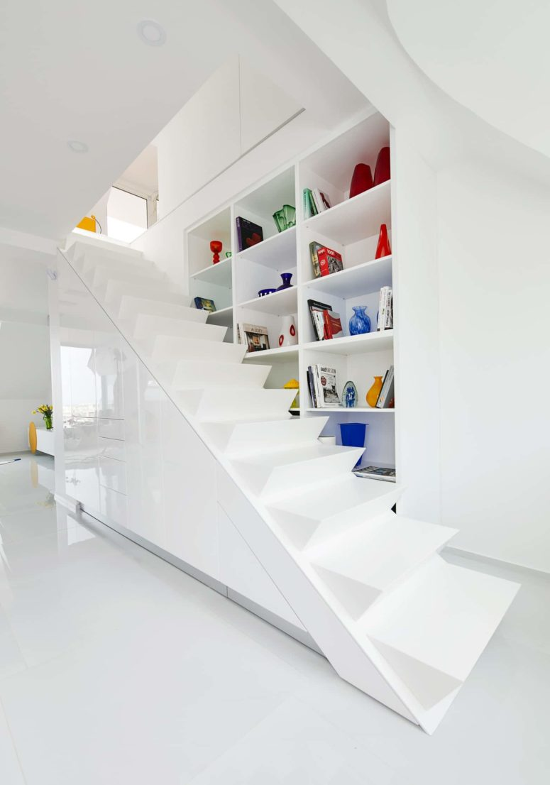 A large staircase in white leads up and there's a large storage unit on the right