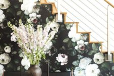 11 a side of the stairs covered with moody floral wallpaper in dark greens and neutrals