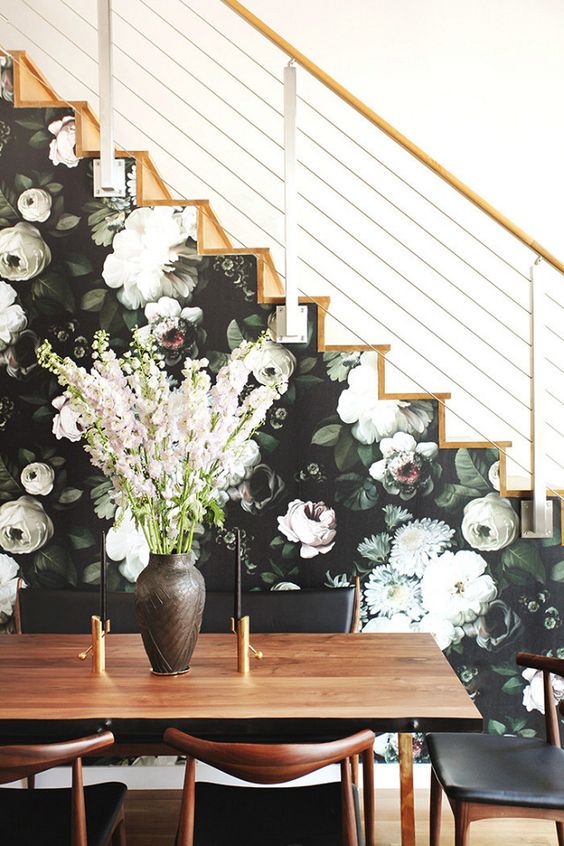 a side of the stairs covered with moody floral wallpaper in dark greens and neutrals