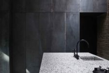 11 a white terrazzo kitchen island looks contrasting in this moody kitchen