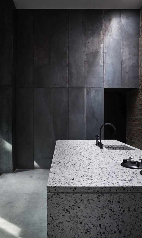 a white terrazzo kitchen island looks contrasting in this moody kitchen