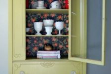 12 a light mustard color cupboard with dark floral wallpaper for a contrast