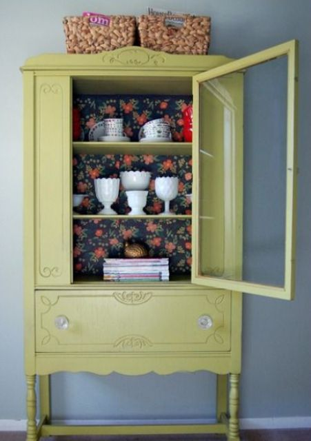 a light mustard color cupboard with dark floral wallpaper for a contrast