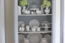14 a grey vintage cupboard with chicken wire on the whole length of doors