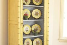 15 a buttermilk cupboard with chicken wire and yellow dishes on display