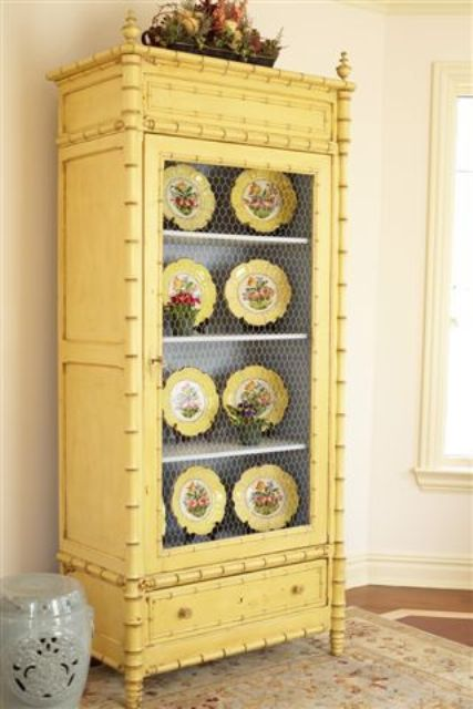 a buttermilk cupboard with chicken wire and yellow dishes on display