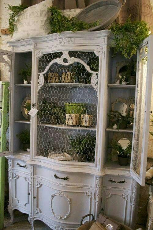 oversized white shabby chic cupboard with chicken wire instead of glass that gives it a unique feel