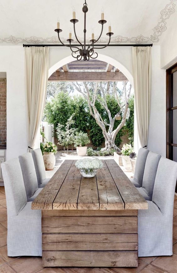 a rustic wooden plank dining table contrasts neutral upholstered chairs