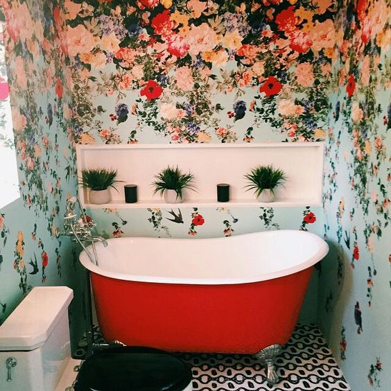 colorful floral wallpaper for a bathroom and a red bathtub that echoes with the walls