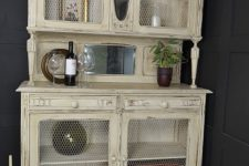 20 a warm pastel cupboard with chicken wire in compartment doors to see the objects better