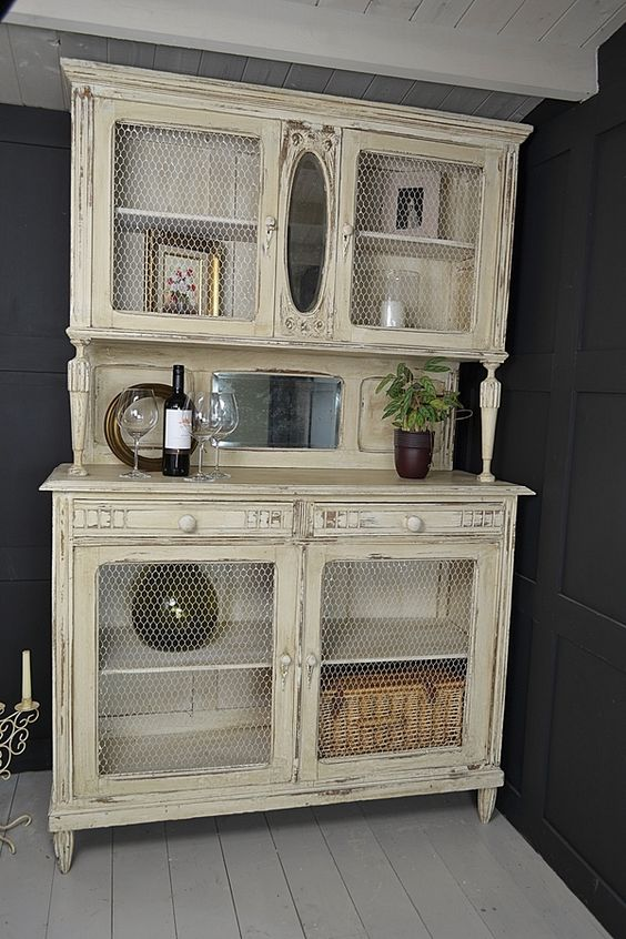 a warm pastel cupboard with chicken wire in compartment doors to see the objects better