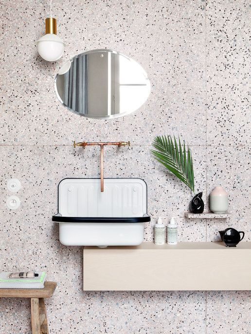 white terrazzo with black dots and copper fixtures for a a chic look