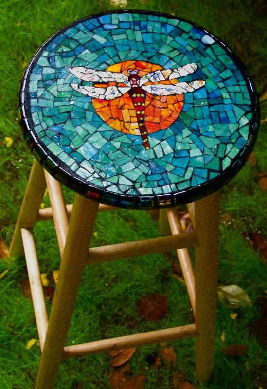 a wooden stool with a colorful dragonfly mosaic on top for a cool look