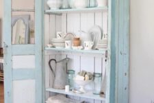22 a pastel blue cupboard with white boards inside is used for storing dinnerware, pitchers and kitchen towels