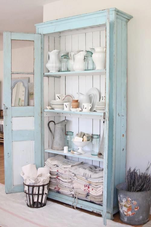 a pastel blue cupboard with white boards inside is used for storing dinnerware, pitchers and kitchen towels