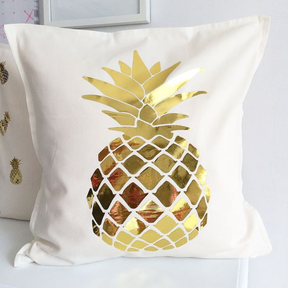 a cream pillow case with a gold pineapple