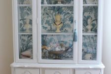 23 a white vintage cabinet with blue and white wallpaper inside for displaying souvenirs