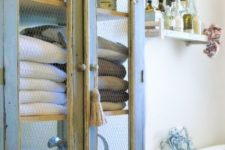 24 a vintage blue and cream cupboard with chicken wire for storing bathroom towels and other stuff