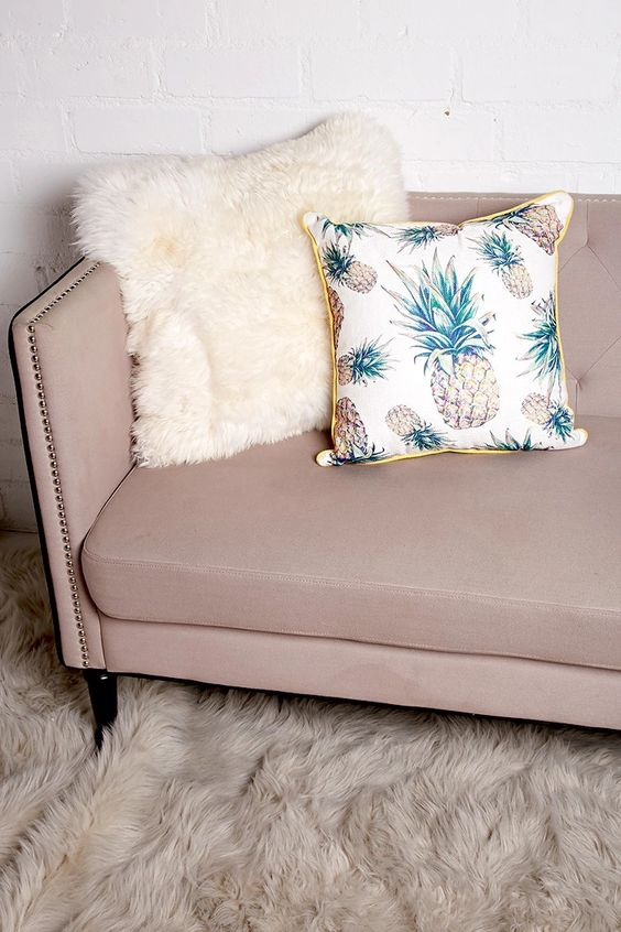 a woven pillow featuring an allover pineapple print, a contrast trim