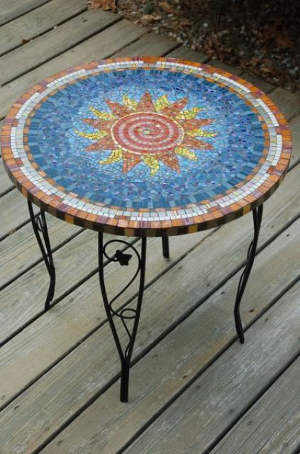 pretty outdoor table with a colorful sun mosaics and on forged legs