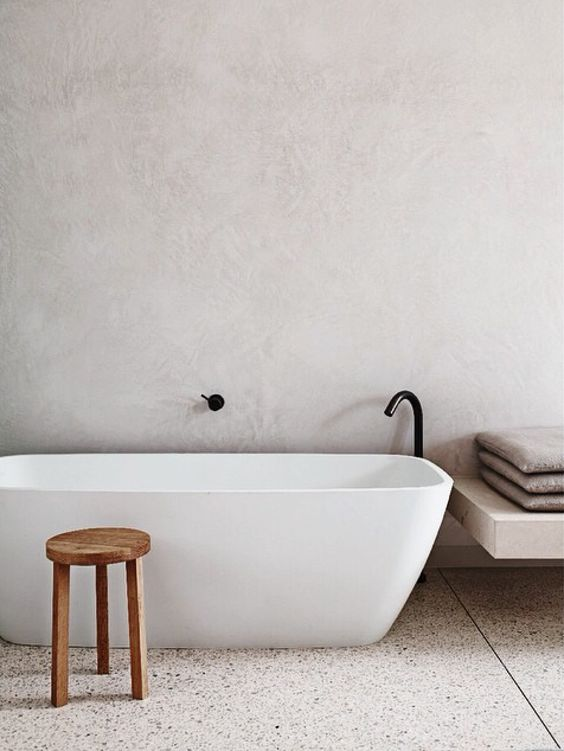 white concrete walls and light colored terrazzo floors for a calming bathroom look