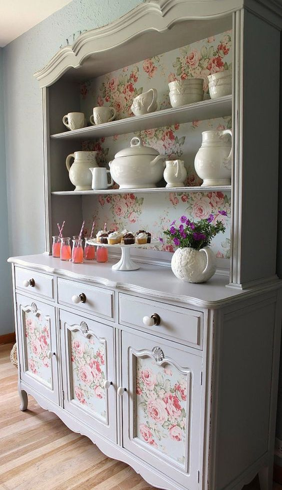 a china abinet with vintage floral wallpaper inside and on the compartments