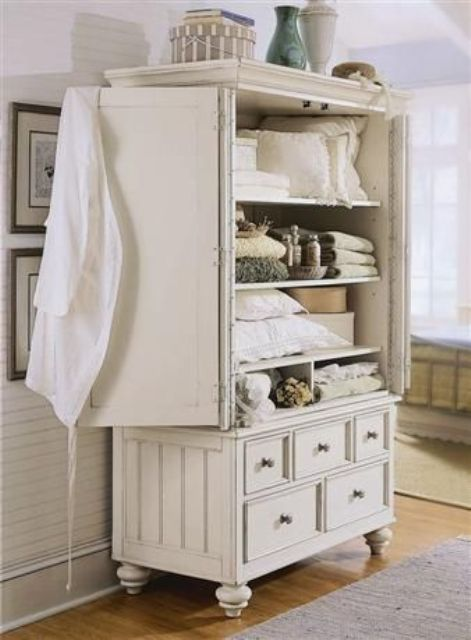 a vintage cupboard in cream for storing bathroom stuff and towels