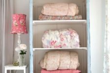 26 a pastel blue cupboard with no doors for storing blankets and bedspreads