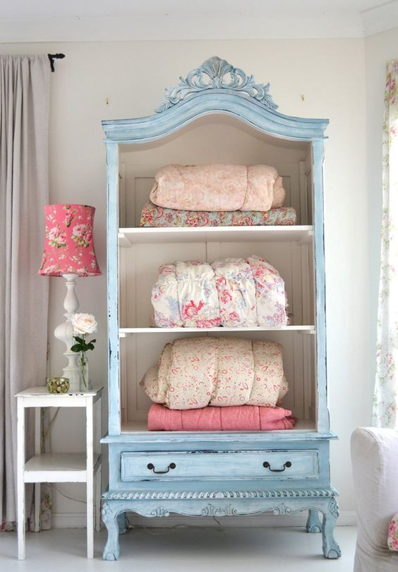 a pastel blue cupboard with no doors for storing blankets and bedspreads
