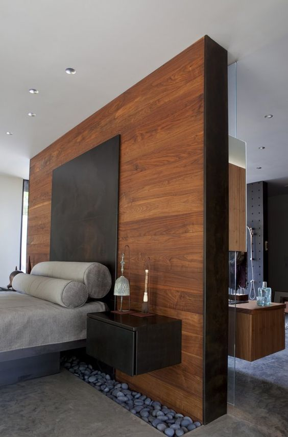 a tall headboard wooden wall acts as a space divider here and makes the bedroom private