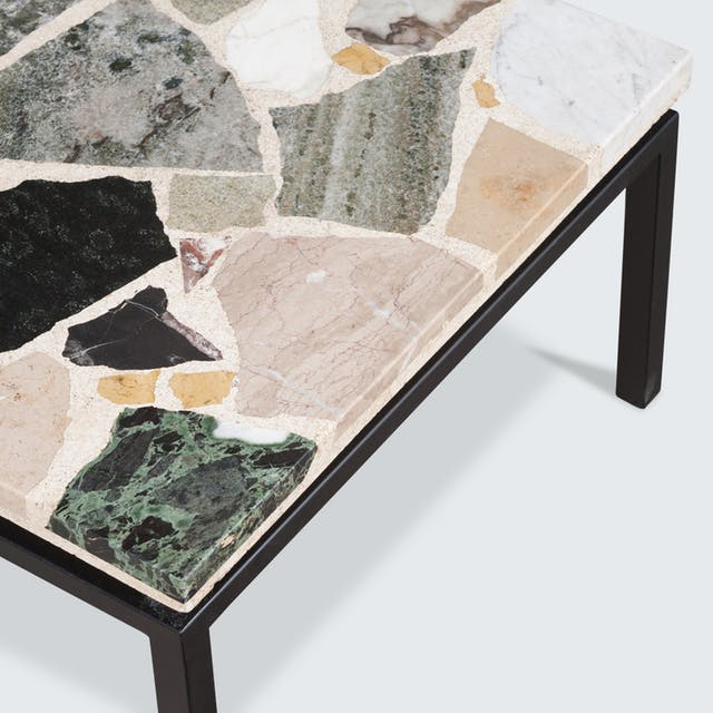 a coffee table with a terrazzo top inlaid with marble, quartz, and granite