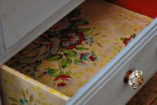 27 colorful floral wallpaper inside the drawers and on the sides for a bold look