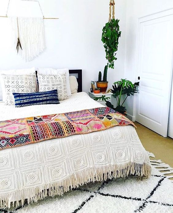 a crochet fringe bedspread, printed pillow covers and a bold boho throw