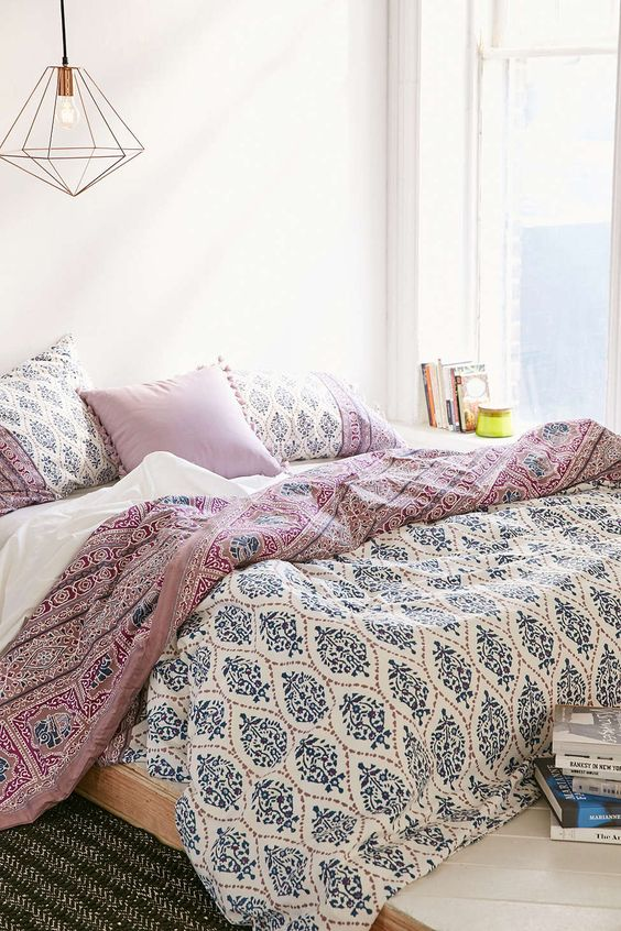 blue, mauve and white printed bedding and tassel pillows