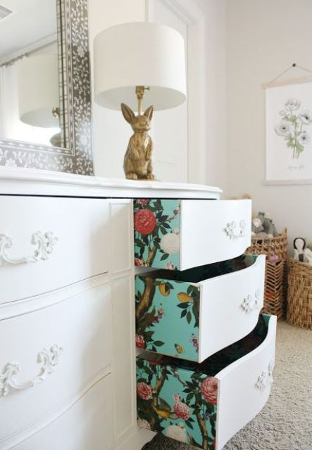 turquoise floral wallpaper lining the drawers of a vintage dresser