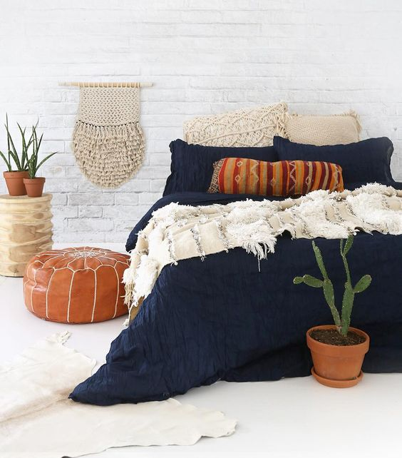textural navy bedding with white crochet pillows and a fringe blanket