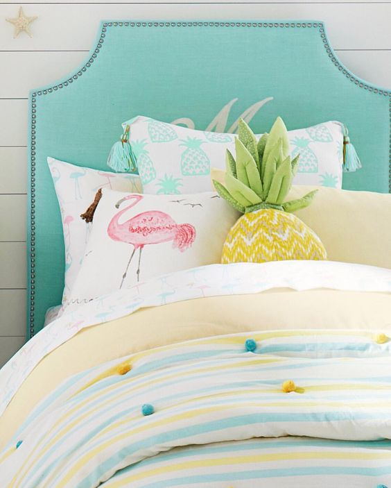 a pink flamingo pillow, a pineapple pillow and colorful pompom bedding