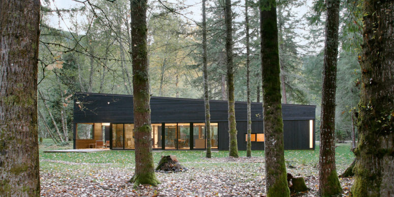 This gorgeous house with a black exterior is located in the forest, on a river and takes the advantage of the views